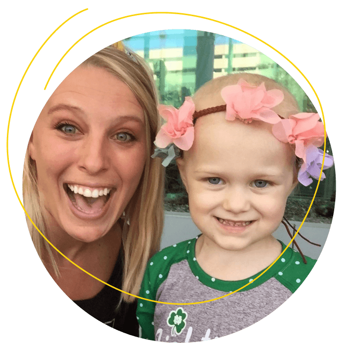 Jess smiling with a little girl wearing a pink and purple flower headband