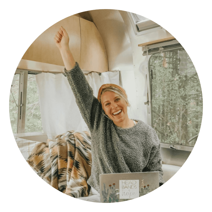 Jess sitting in her airstream with her laptop open smiling at the camera pointing her fist up in the air cheering
