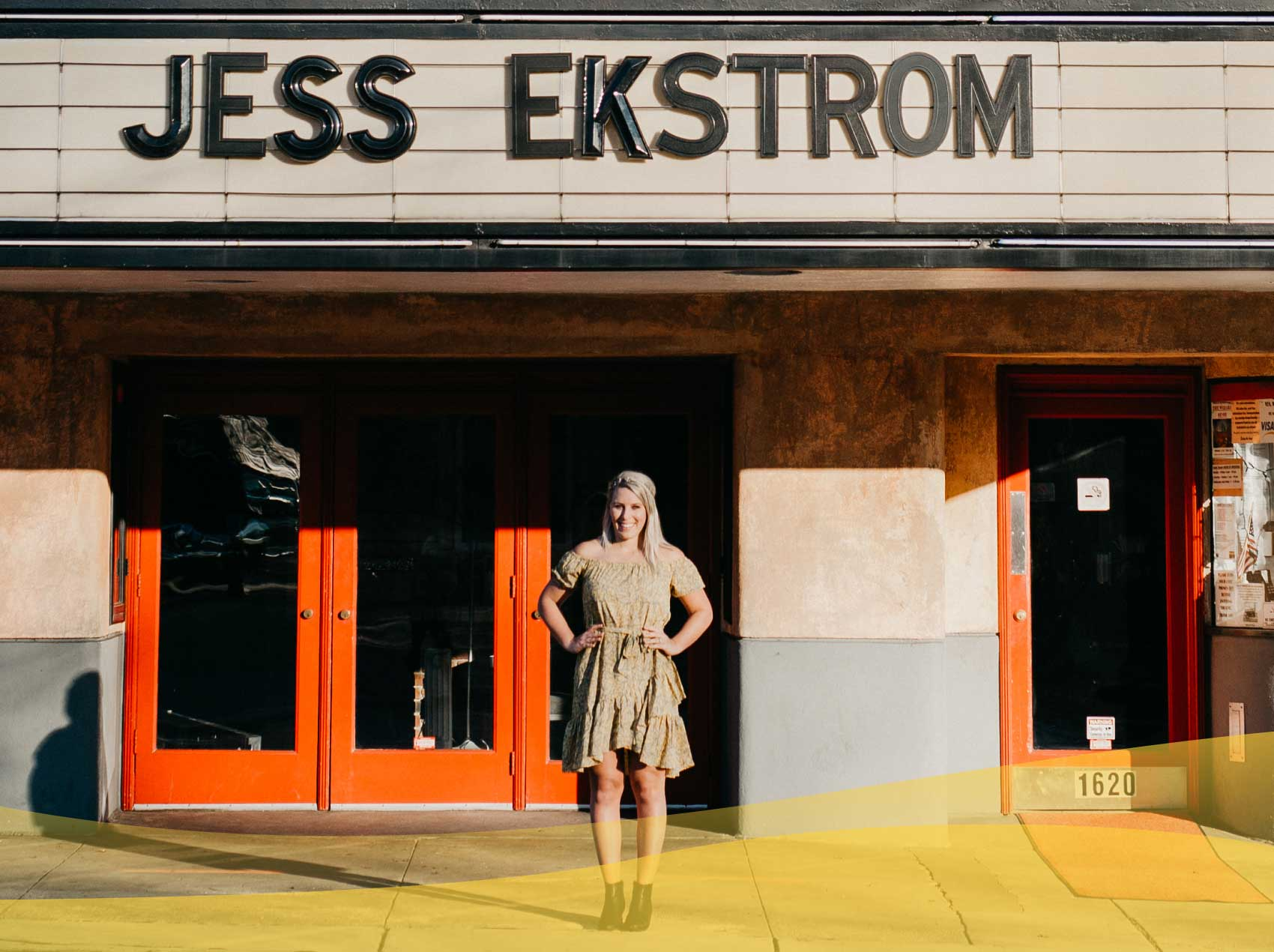 Jess Ekstrom standing outside of a building with a sign that has her name in big letters