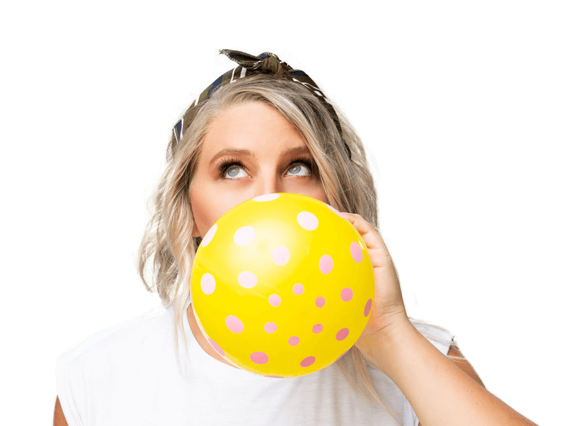 Jess looking up while blowing up a yellow balloon with pink polka dots in front of blue background